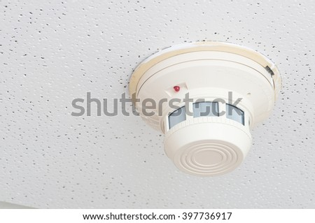 Smoke detector on a white ceiling - stock photo