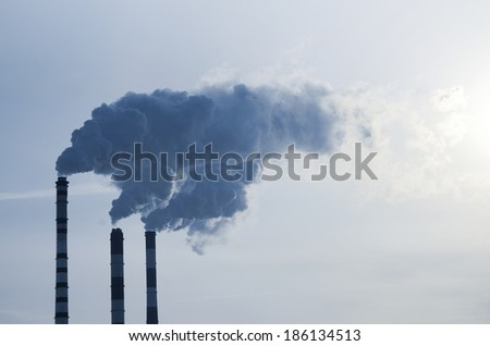 Smoke emission from factory pipes on blue sky - stock photo
