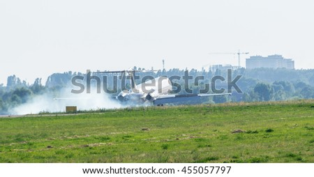 Smoke emitting from airplane wheel while landing on runway in International Airport. Aviation copy space background.  - stock photo