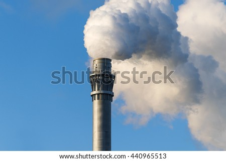 smoke from an industrial chimney against the blue sky with copy space - stock photo