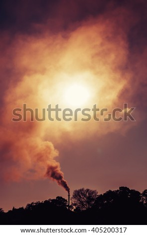 Smoke from an industrial smokestack blocking out the morning sun - stock photo