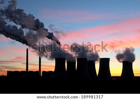 smoke from coal power plant under sunset sky - stock photo