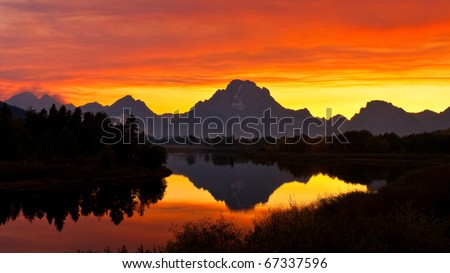 Smoke from forest fires created intense sunset colors at Oxbow Bend on the Snake River.  Grand Teton National Park, Wyoming. - stock photo
