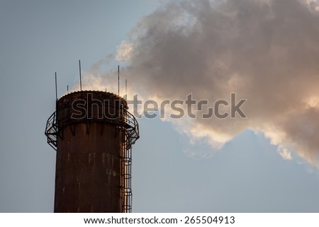 Smoke from high pipes against the sky - stock photo