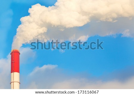 Smoke from the chimney on blue sky background. - stock photo