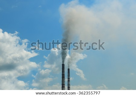 smoke from the pipes against the blue sky - stock photo