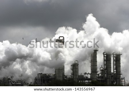 Smoke of heavy industry is highlighted by the sun. Shot in the Dutch industry area of the Europoort - stock photo