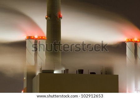 Smoke originating from a large power-station at night - stock photo