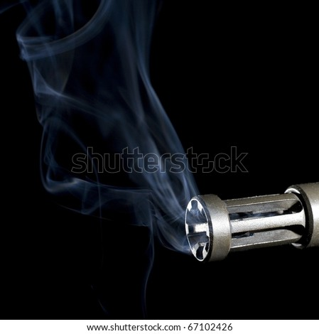 smoke rising from a flash hider on an assault weapon - stock photo