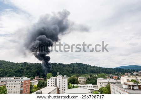 Smoke rising near residential buildings. Forest fire. - stock photo