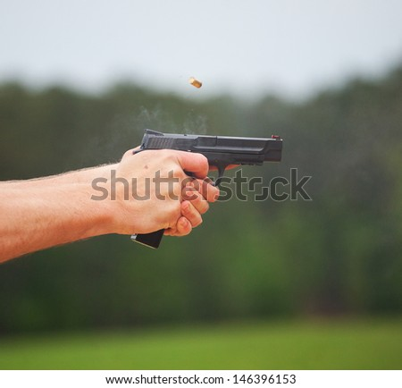 Smoke rising off a handgun just after a shot is taken - stock photo