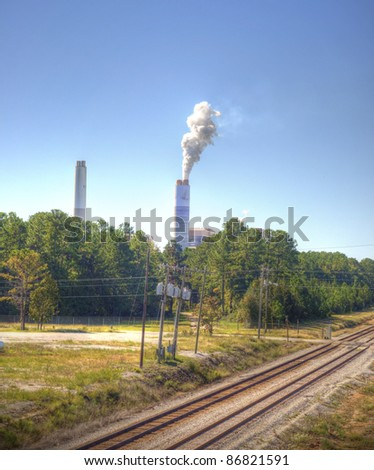 Smoke Stack with White Smoke Behind Train Tracks. - stock photo