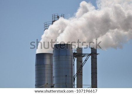 Smoke stacks billowing out steam and vapor from a manufacturing facility - stock photo