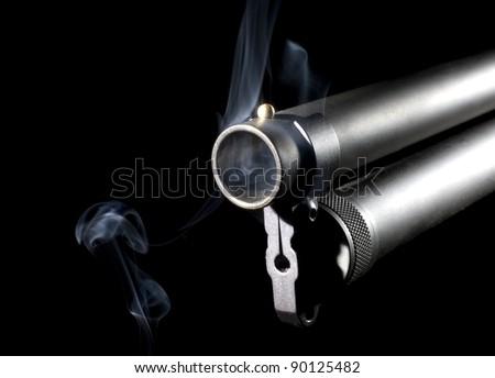 Smoke staying around a shotgun barrel after a shot was taken - stock photo