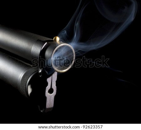 smoke that is coming from a 12 gauge shotgun barrel that is rising - stock photo
