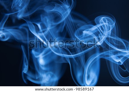 Smoke winding loops on a black background - stock photo