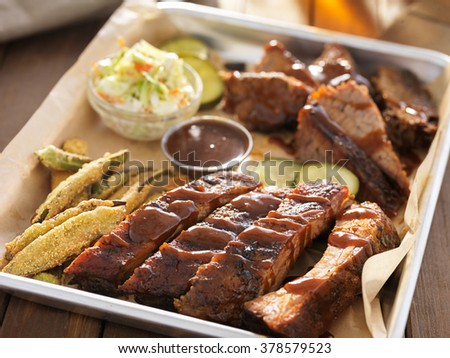 smoked beef brisket with barbecued ribs in platter and fixings - stock photo