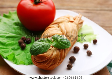 Smoked braided cheese on wooden table - stock photo