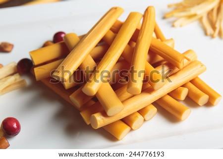 Smoked cheese sticks on white plate - stock photo