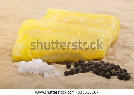 smoked cod with coarse salt and pepper on brown kitchen paper - stock photo