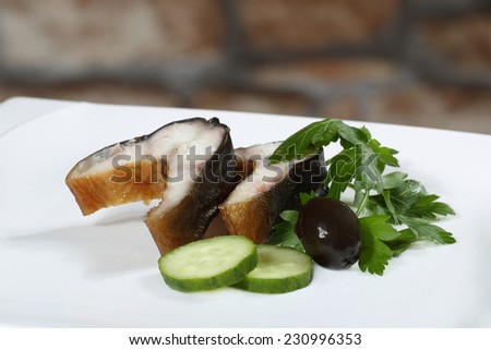 Smoked eel pieces served on plate as appetizer on blurred stone wall background. Image for a restaurant snack menu or party invitation cover design  - stock photo