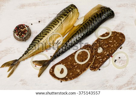 Smoked fish (mackerel, Scomber) on white background with rye bread, onion and black pepper - stock photo