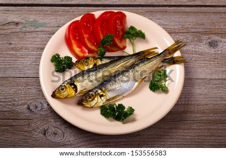 Smoked fish with tomatoes on plate top view - stock photo