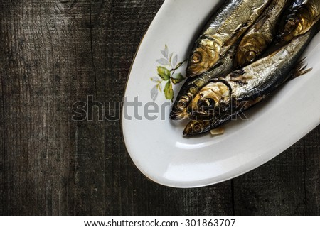 Smoked herring on a white plate on old weathered wooden table - stock photo