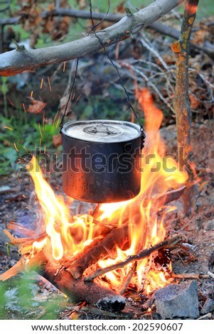 smoked kettle on tourist camp fire - stock photo