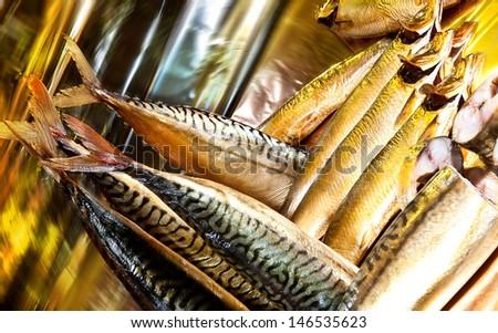 Smoked mackerel on yellow mirror background - stock photo