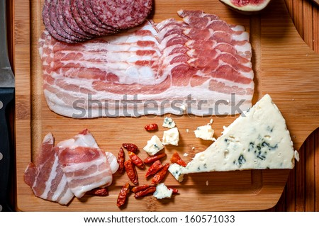 smoked meat, salami, ham, sausages with bacon and fancy cheese on wooden plate - stock photo