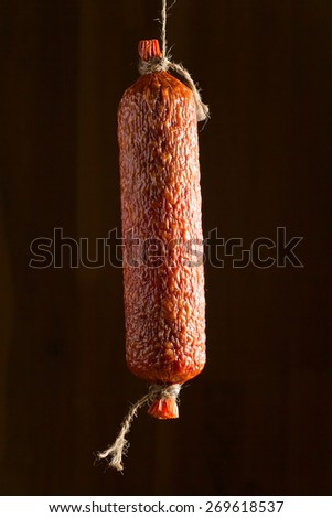 smoked salami on a background of wooden wall - stock photo