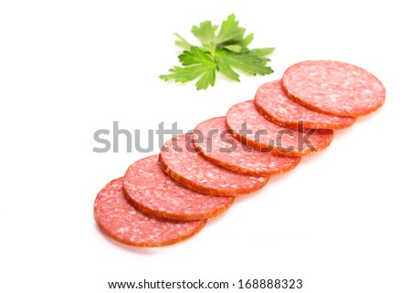 Smoked salami sausage. Sliced smoked sausage salami isolated on white background. Pieces of smoked sausage decorated with parsley leaves. Neatly sliced smoked sausage for advertising. Space for text. - stock photo