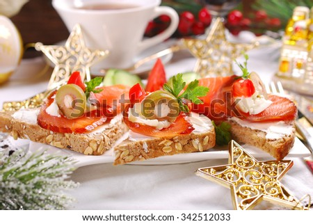 smoked salmon and cream cheese canapes as appetizer for christmas - stock photo