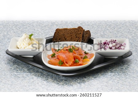 Smoked Salmon Lox platter with red onion, rye bread, and cream cheese. - stock photo