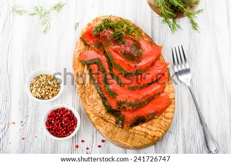 Smoked salmon marinated with fresh dill and spices on wooden board - stock photo