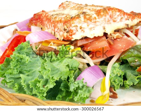 smoked salmon on salad of lettuce, tomato, onion, pepper, kale, bean sprout, and beats - stock photo