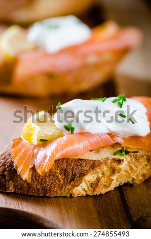 smoked salmon on toasted bread with cream fresh, lemon and chives on white plate - stock photo