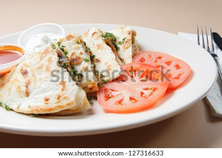 Smoked Salmon Quesadillas served with tomatoes and dipping sauces - stock photo