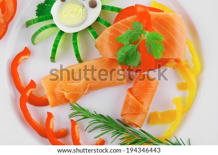 smoked salmon slices with vegetables over white plate - stock photo