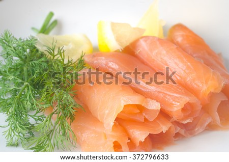 smoked salmon with lemon and herbs - stock photo