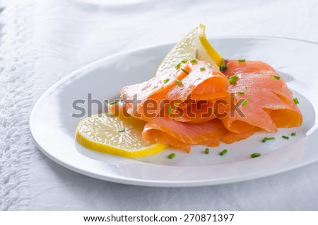 smoked salmon with lemon slices on white plate - stock photo