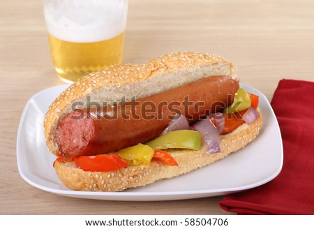 Smoked sausage on a sesame seed bun with peppers and onions and a beer in the background - stock photo