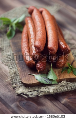 Smoked sausages and basil leaves on a rustic cutting board - stock photo