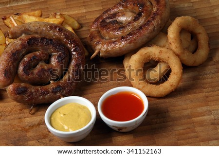 smoked sausages domestic hot - onion circles and baked potatoes seasoned - barbecue sauces - American food - fast food - stock photo