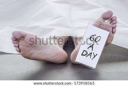 smoker, feet of a deceased man under white blanket with a toe tag that reads 60 a day - stock photo