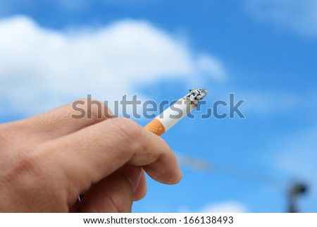 Smoker hand on the blue sky background - stock photo