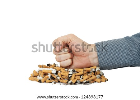 smoker's fist on heap of cigarettes - stock photo