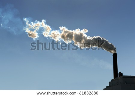 Smokestack billowing smoke into the atmosphere - stock photo