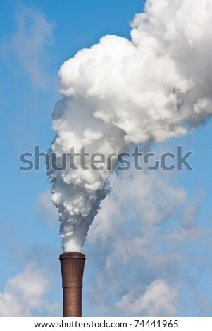 Smokestack with heavy pollution against a blue sky - stock photo